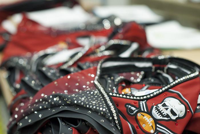 The Line Up - Tampa Bay Buccaneer Cheerleaders Signature Costume - Applying rhinestones to the costume